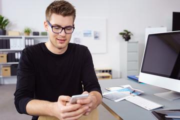 junge mann im büro tippt eine nachricht