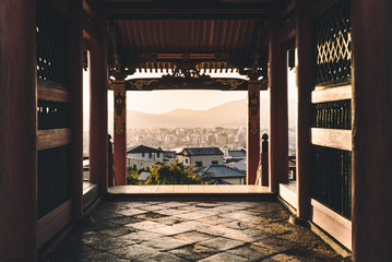 Through old and new - City view framed by ancient pagoda at sunset.