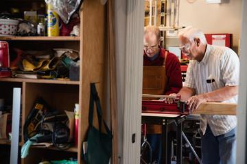 Senior men placing woodblock on carpentry equipment workshop