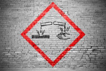Ziegelsteinmauer mit GHS-Piktogramm ätzend für Gefahrstoffe Graffiti
