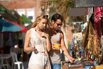 Couple eating frozen yoghurt and browsing jewellery stall at Venice Beach, California, USA