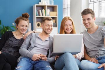 freunde schauen zusammen auf laptop