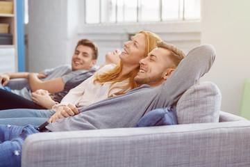 lachende freunde liegen auf dem sofa