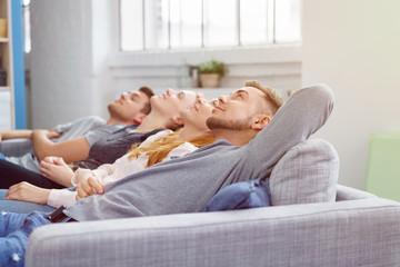 freunde liegen entspannt zu hause auf dem sofa