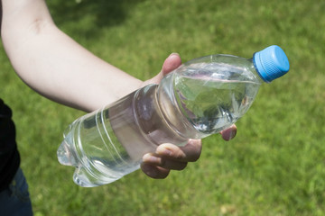 Plastic bottle with water in the men's hands on a background of green grass