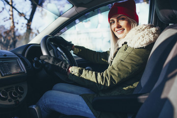 Portrait of happy young woman in warm clothing driving car