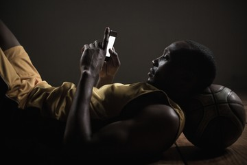 Portrait of basketball player lying and using his smartphone
