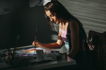 Female artist painting at table in art studio