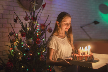 Girl carrying cake with candles in front of Christmas tree