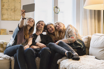 Happy family of four taking selfie through digital tablet at home