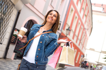 young woman in the street with a coffee and shopping bags