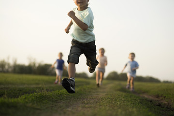 Low view of a boy running in a field with other children behind