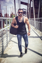 Handsome muscular man standing outdoor in city