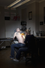 A female tattoo artist tattooing a man's back in a tattoo shop