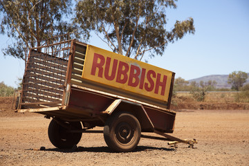 A vehicle trailer with the word Rubbish on it