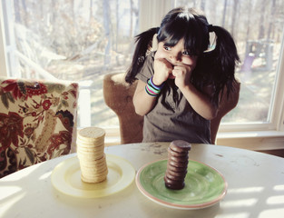 A girl trying to decide between two stacks of vanilla and chocolate cookies