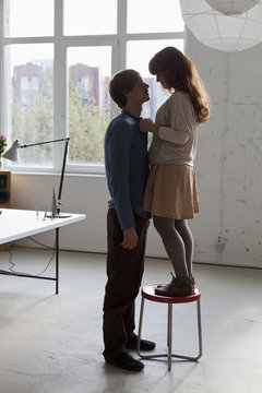 A young woman standing on a stool facing her tall boyfriend