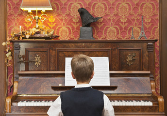 A boy practicing on an upright piano