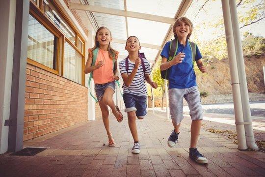 Happy school kids running in corridor