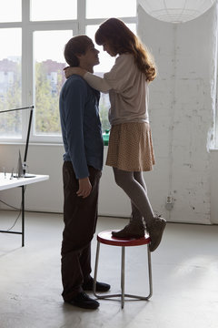 A woman standing on a stool with her arms around her tall boyfriend