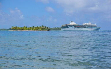 Cruise ship with a tropical islet at the horizon, Huahine island, Pacific ocean, French Polynesia