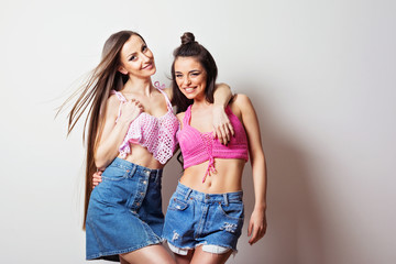 Two beautiful young women in crochet tops and denim skirt and shorts