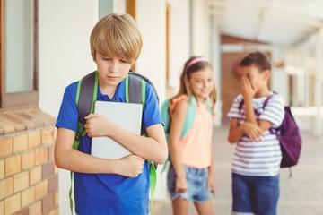School friends bullying a sad boy in corridor