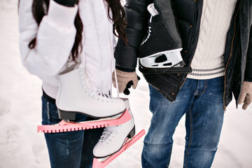 young love couple holding his skates on the shoulder. winter holidays