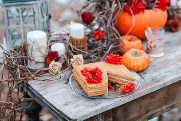 halloween inspiration. Autumn still life. pumpkin, dry roses, viburnum honey cake. in a vase. twigs. on the table