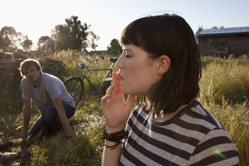 Girl smoking in field as guy in background watches