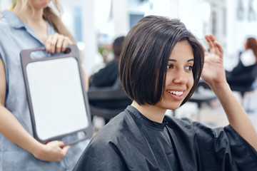 Closeup portrait of hispanic latin girl woman sitting in chair in hair salon looking in mirror at her new haircut, short bob pixie, happy joy emotion