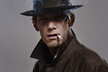 Portrait of a man wearing a hat and trench coat while smoking