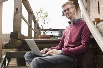 A man with a laptop sitting on a staircase