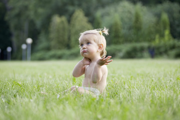 A baby girl sitting on grass in a diaper and looking confused