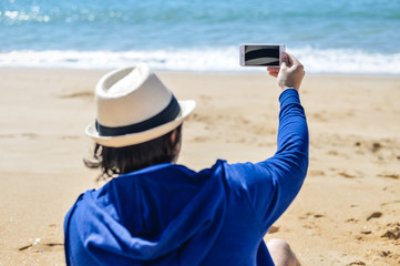 Back view shot of man holding smartphone photographing beach background