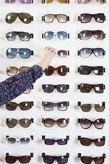 A human hand choosing a pair of sunglasses in an eyewear store