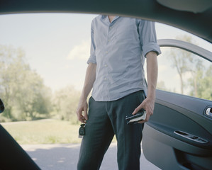 A man standing outside a car, midsection