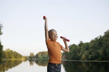 A girl lifting hand weights on a wooden jetty