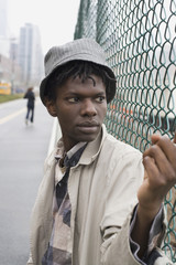 A young man leaning against a chainlink fence