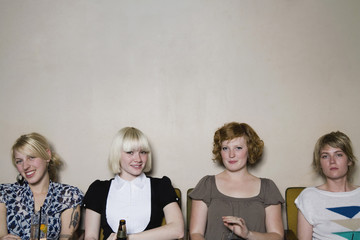 Four young woman sitting against a wall in a bar
