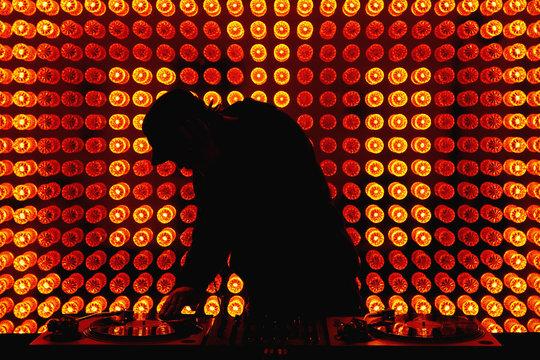 A DJ scratching a record in a nightclub