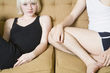 A young couple sitting on a sofa together