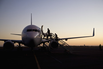 People boarding an airplane at dusk