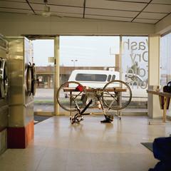 A bike upside down in a laundromat