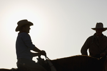 Silhouette of two cowboys sitting on horses