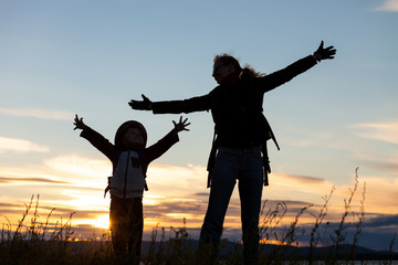 Mother and son playing on the coast of lake  of at the sunset ti