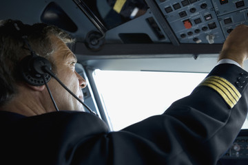 A pilot in the cockpit of a commercial plane