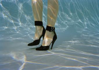 A woman's legs wearing high heels underwater