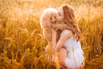 Beautiful  girl  with his dog on the field in sun light.