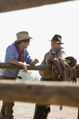 Two ranchers talking next to a fence
